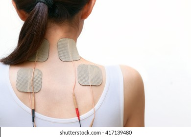 Patient woman is doing massage of electrical stimulation ( TENs ) for the neck and upper back