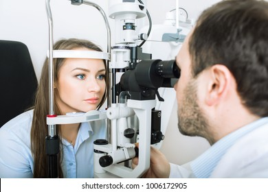 patient woman having her eyes examined by an optometrist using medical equipment, in ophthalmology clinic.