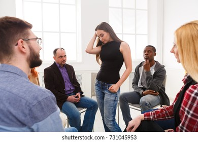 Patient woman standing in circle and telling her problems to therapy group, copy space