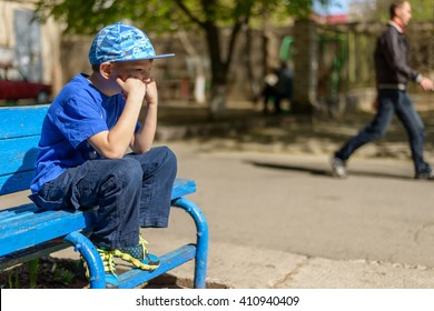 Patient young boy sitting waiting on a blue wooden outdoor bench in a trendy blue outfit with his hand to his chin and a bored expression