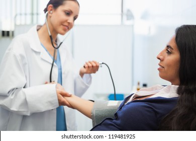 Patients blood pressure being checked by doctor in hospital room