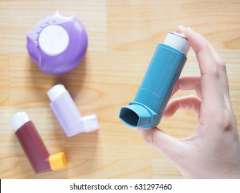 Patient's hands holding blue asthma inhaler with set of asthma/COPD inhalers on wood table. Pharmaceutical products for treat lung inflammation and relief asthma attack. Health and medical concept.