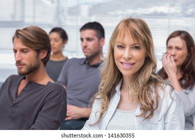 Patients listening in group therapy with one woman smiling sitting in chairs in office