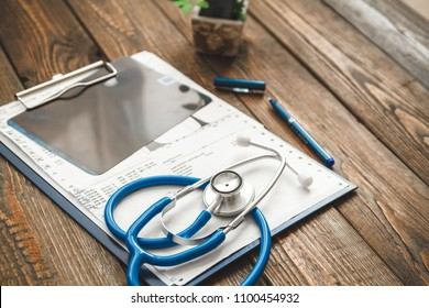 Patient's medical card and x-ray picture on a wooden table close-up