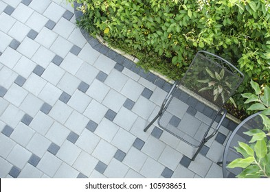 Patio blocks with chair and green background.