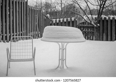 A patio chair and snow covered table sits absurdly in a backyard winter scene