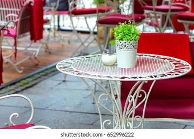 patio of an european restaurant - colorful tables and chairs with pillows and blankets on the street, outside