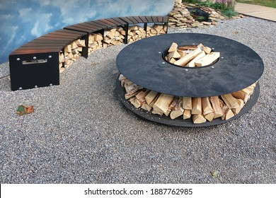 Patio Fire Pit Round Table With Log Holder On The Stone Or Gravel Surface. Iron Rounded Fire Pit With Grill Top On Backyard Party Place. Grill Appliance And Fireplace On The Backyard. Iron Furniture.