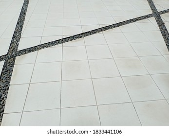 The patio floor is designed with white tiled and crevices, with small black stones inserted in the crevices.