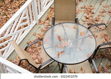 Patio furniture covered with fall leaves on a back deck.  The photo is taken from above.