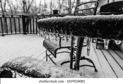 Patio and furniture frozen over Kentucky's ice storms on deck black and white-natures photography. Season.