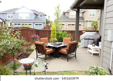 Patio furniture and grill in the backyard of a home.