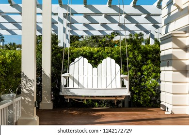Patio lounge white wooden new hanging swing in outdoor spring green garden in backyard porch of home zen, hanging furniture, nobody in Florida tropical cottage vacation home