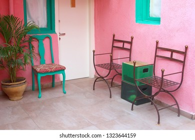 Patio with metal chairs, pink walls and table made from beer crates