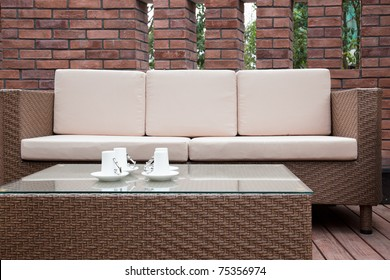 Patio with an outdoor sofa and table against the red brick wall.