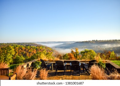 A patio overlooks an Ozarks valley with fall foliage and fog as the morning sun rises.