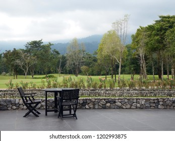 Patio table and chairs with a view across a golf course to forest and mountains in the Khao Soi Dow district of eastern Thailand.