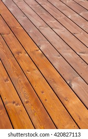 Patio wooden deck floor freshly stained with wood oil. Before and after varnishing effect.  Home improvement concept.