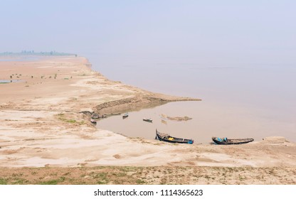 Patna, Bihar, India. View of the river Ganges with boats moored along the bank and mud flats on a hot day as seen from the Mahatma Gandhi Seti (bridge) near Patna, Bihar, India.