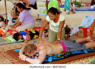 Patong / Phuket, Thailand - January 6, 2007:  Western tourists lying on mats getting a massage on Patong Beach from two Thai women
