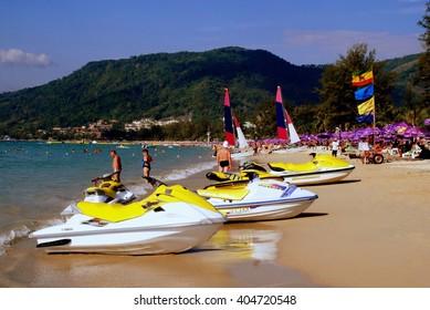 Patong / Phuket, Thailand - January 9, 2007:  Catamarans with large sails and rental jet ski boats sitting on sandy Patong Beach