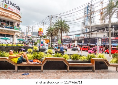 Patong, Thailand - 9th August 2018: Man relaxing on a bench outside the Jung Ceylon shopping mall.  The mall serves mainly holidaymakers.