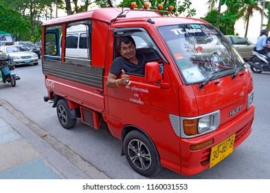 Patong, Thailand - October 15, 2014: Red tuk-tuk and smiling driver on Thawewong Road.