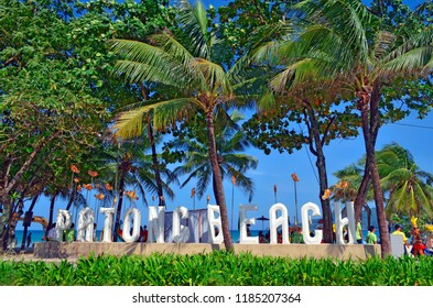 Patong, Thailand - October 16, 2014: The Patong Beach white sign on Thawewong Road with the beach in the background.