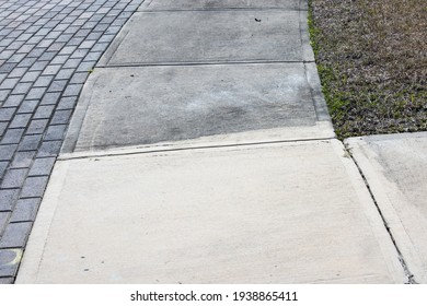 Patrially cleaned and partial irty cement sidewalk in front of a homeafter some of it has been pressure washed.