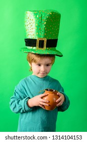 Patrick boy. Child in top hat holds pot with gold. Green top hat. Leprechaun. Green leprechaun. St Patrick's Day. Green hat with clover. Traditions of Saint Patrick Day. Sale. Discount. March.