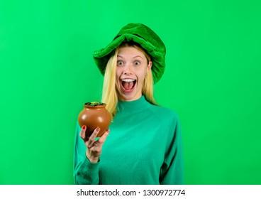 Patricks Day. Happy girl in green top hat holds pot with gold. Saint Patrick's Day. Leprechaun. Irish Traditions. Green top hat. Green hat with clover. Leprechaun costume. Clover.