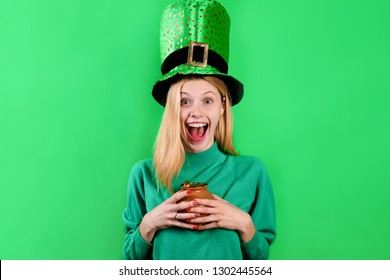 Patrick's Day. Happy girl in green top hat holds pot with gold. Saint Patrick's Day. Leprechaun. Irish Traditions. Green hat with clover. Clover. Pot with gold. Gold. Green top hat.