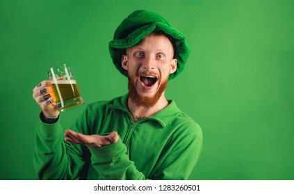 Patricks day party. Portrait of excited man holding glass of beer on St Patrick's day isolated on green. Man in Patrick's suit smiling
