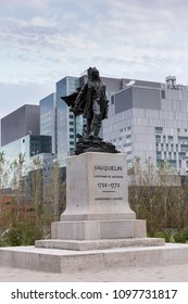 Patrimonial Eugene Benet 1930 bronze statue in the Vauquelin square, with modern buildings in the background, Old Montreal, Quebec, Canada, September 10, 2017