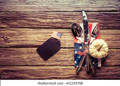 Patriotic American autumn or fall place setting with a knife, spoon and fork on a Stars and Stripes napkin with a blank gift tag with an American flag, rustic wood background and vignette