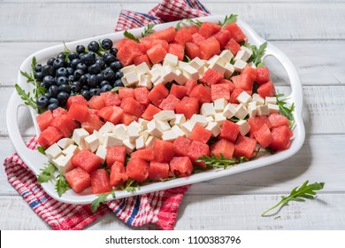 Patriotic American flag salad with blueberry, watermelon and feta on arugula