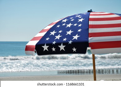 Patriotic beach umbrella at the seashore.