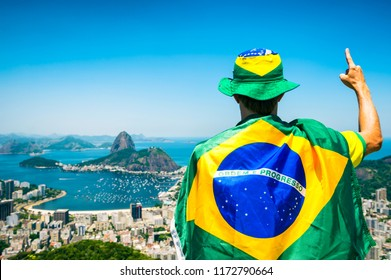 Patriotic Brazilian fan wrapped in flag holding up hand with 'number 1' signal at Sugarloaf Mountain Botafogo view Rio de Janeiro. Translation: Order and Progress