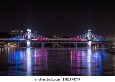 A patriotic bridge lit up at night with the colors of the American flag; red, white, and blue over the Brazos River in Waco, Texas.