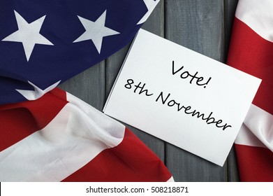 Patriotic Call - Vote November 8. USA presidential elections 2016. American flag and sheet of paper with remainder on a wooden background.