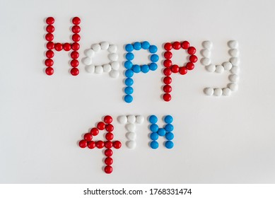 Patriotic colored red, white and blue button shaped chocolates spelling out 'Happy 4th' on a white background. Ideal for America's Holiday, Fourth of July Independence Day