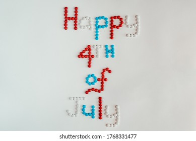 Patriotic colored red, white and blue button shaped chocolates spelling out 'Happy 4th of July' on a white background. Ideal for America's Holiday, Fourth of July Independence Day