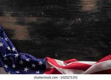 Patriotic composition w/ ruffled American flag, wood planks background. United States of America stars & stripes symbol, copy space for text. 4th of july Independence day concept. Background, close up