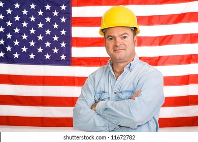 Patriotic construction worker standing in front of an American flag.  Photographed in front of flag, not composite image.