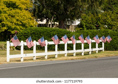 Patriotic display of American flags waving on white picket fence next to a road. Typical small town Americana Fourth of July Independence Day decorations.