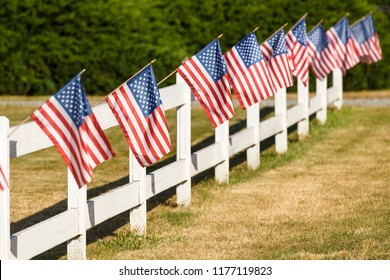 Patriotic display of American flags waving on white picket fence. Typical small town Americana Fourth of July Independence Day decorations.