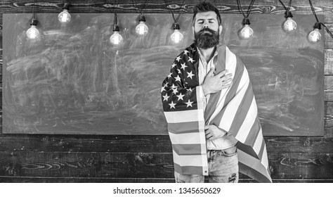 Patriotic education concept. Teacher teaches to love homeland, USA. Man with beard and mustache on serious face with flag of USA, chalkboard on background. American teacher covered with american flag.