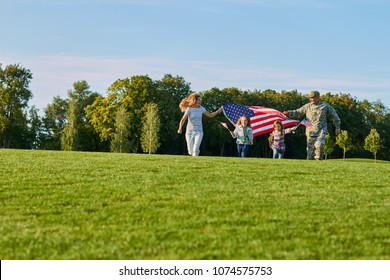 Patriotic family with huge usa flags outdoors. US soldier with his family in the park.