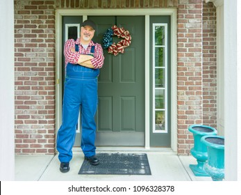 Patriotic farmer celebrating 4th July Independence Day standing with folded arms in front of the door of his farmhouse decorated with a wreath in the national colors