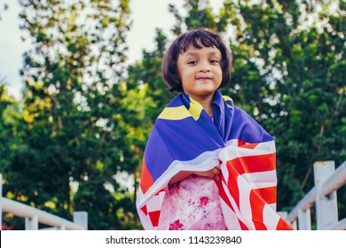 Patriotic girl with Malaysian flag in spirit of Merdeka (Independence Day)